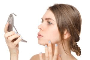 Woman examining her face in a handheld mirror