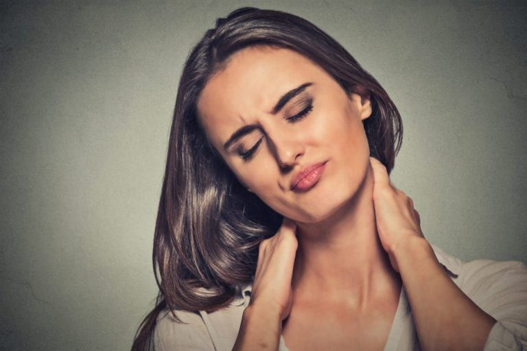 Woman holding her neck in discomfort