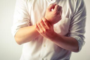 Man holding wrist in pain from gout